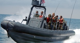 030922-N-8209D-010 San Diego, Calif. (Sep. 22, 2003) -- Slicing across the surface of the water, members of Special Warfare Combat Craft (SWCC) Class 45 familiarize themselves with the maneuvering capabilities of their Ridged Hull Inflatable Boat (RHIB) during a day of training off the Pacific coast.  U.S. Navy photo by Photographer's Mate 3rd Class John DeCoursey.  (RELEASED)
